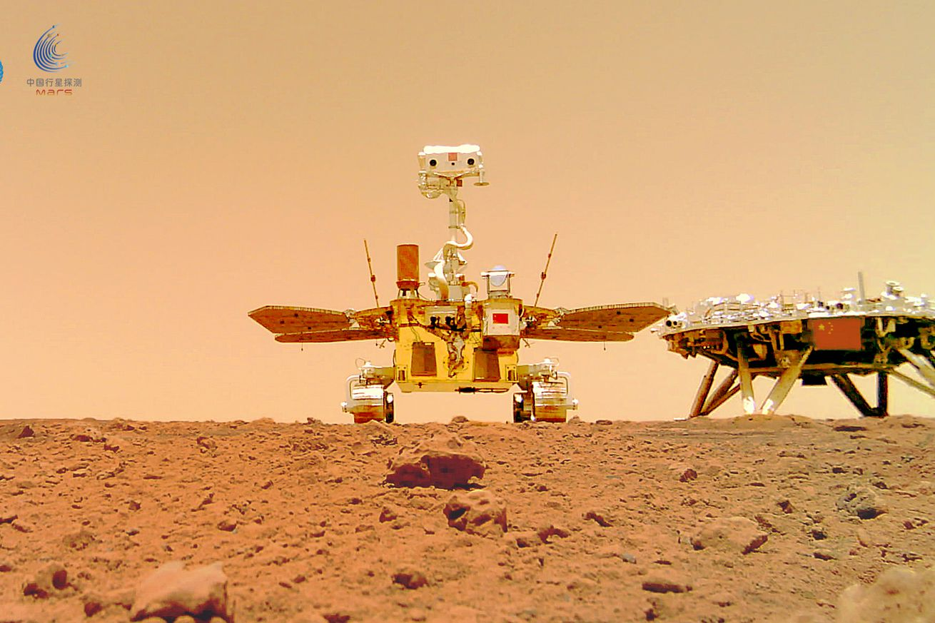 The rover sits in the center of the photo, which is angled upward from the red martian surface. To its right is the landing platform.
