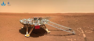 A landing platform with a ramp coming down from it sits among a red-orange landscape.