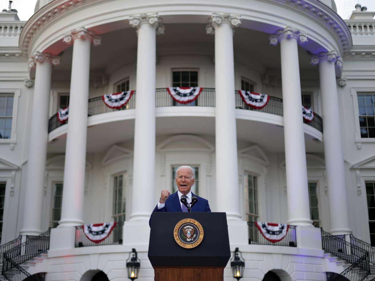 President Biden speaks from behind a lectern and in front of the White House, which is festooned with red, white, and blue bunting.