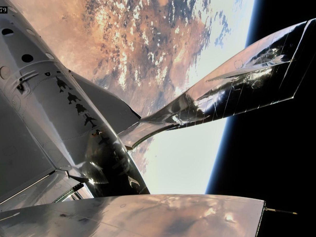 The wing of an orbiting spaceship with Earth and black space behind it.