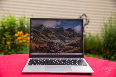 The Framework laptop open, outdoors, on a red tablecloth with a garden and the wall of a house in the background. The screen displays a mountainous landscape.